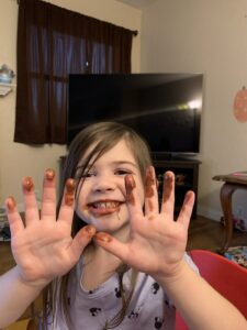 Girl with chocolate on faces and finger